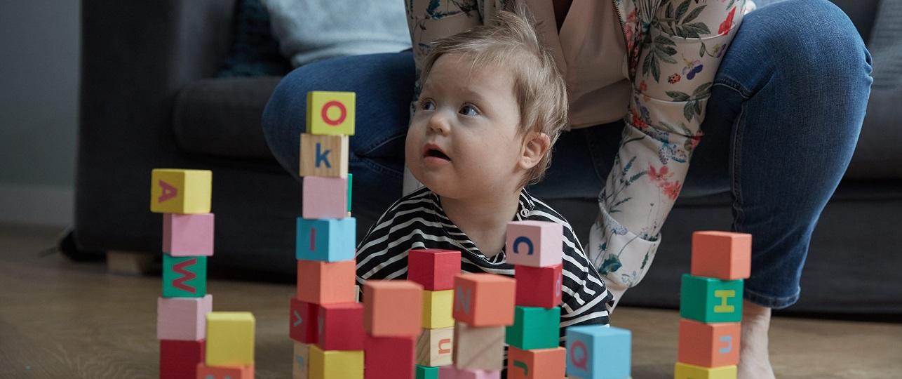 Criança brincando com bloquinhos enquanto é segurado pela mãe