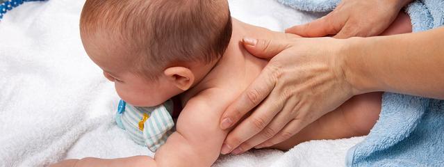 Manos masajeando la espalda del bebe