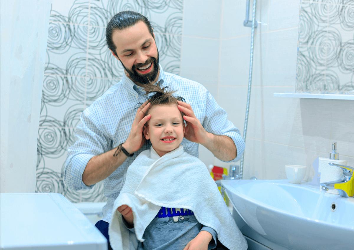 Papá se ríe con su hijo al peinarle el pelo